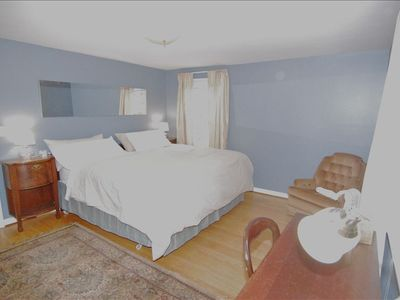 Master bedroom with king size bed, writing desk, reading chair and ample closets