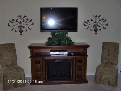 TV with electric fireplace in den.