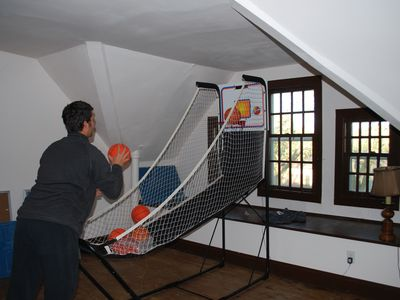 The attic game room features a piano, pop-a-shot game, another TV and seating