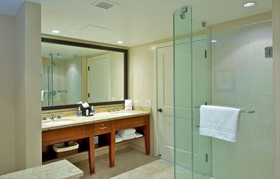 Second bedroom bathroom with dual sinks and enclosed glass shower & tub
