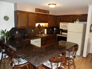 Dillon condo photo - Full kitchen showing granite backsplash with mountain peaks