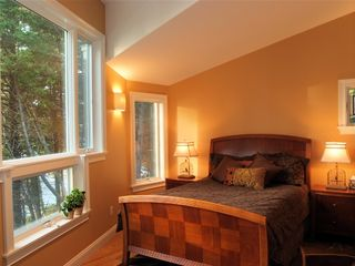 Bath house photo - Bedroom with architectural window w/water view
