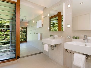 Bathroom 1 with double shower & vanities, overlooking vegetation