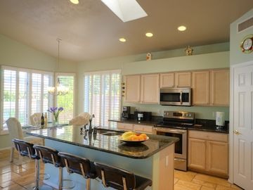 Kitchen and dining area showing counter seating plus dining table. Lake views.