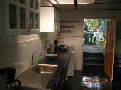 Dominical cottage rental - kitchen counter, stove, refri, entrance to patio