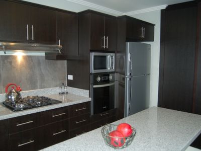 Kitchen includes all appliances. Cabinets to the right enclose stacked washer/dryer and laundry sink