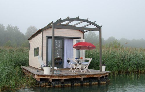 Small apartment on the water with boat in the water.