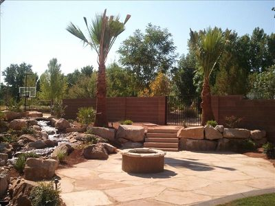 backyard water feature with patio, wood fireplace, basketball in distance