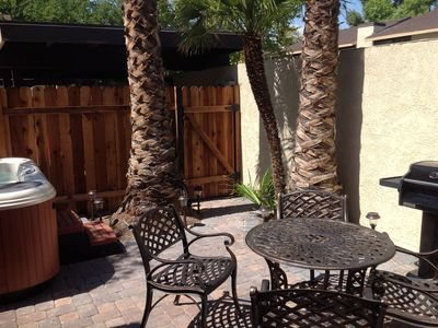 Private backyard with dining area, spa, grill, and gate to covered parking