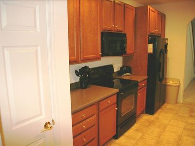 Kitchen with spacesaver appliances and lots of cabinets, pantry