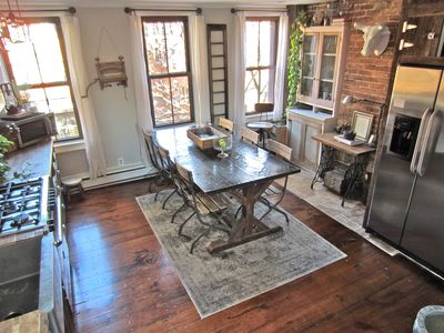 Custom rustic kitchen with 36' gas range, farm table and stainless appliances