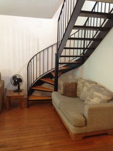 Iron stairway to upper floor bedroom and outside deck.