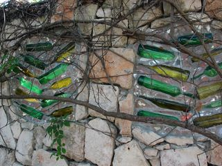 Akumal villa photo - stone wall with bottles around property with vines and roots growing on it