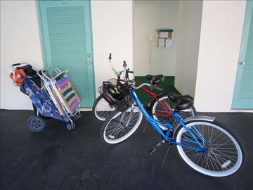Covered carport area with bikes and beach cart in front of large storage locker