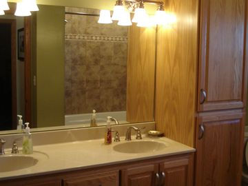 Spacious tiled bathroom with large mirror and double sinks