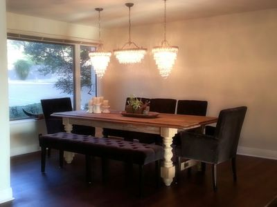 Dining room with plenty of seating for 8 features elegant triple chandeliers