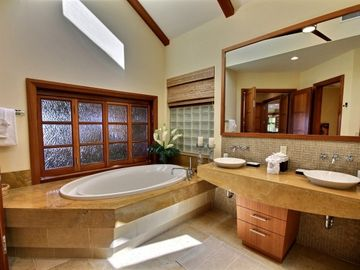 Jetted 2-person spa tub, double vessel sinks, roomy travertine walk-in shower
