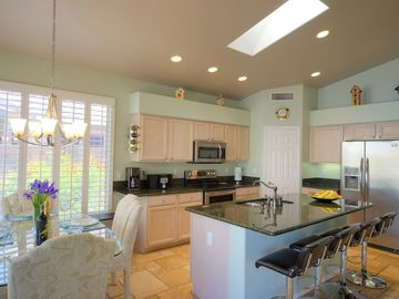 Kitchen area showing skylights, stainless appliances and slab granite counters.