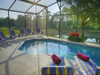Pool deck equipped with 8 loungers and 8 patio chairs. Conservation view - Emerald Island villa vacation rental photo