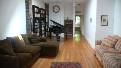 front room with sky light, two ceiling fans, comfy couches, and baby grand piano