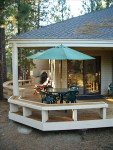 Newer wrap-around-deck with built-in benches, umbrella table with chairs and BBQ
