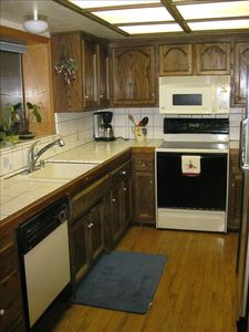 Kitchen area with dishwasher, stove microwave, coffee maker