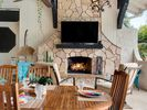 Cozy up by the outdoor fireplace with a large TV