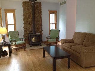 Utica house photo - Living room features wood burning fireplace and many windows with river views
