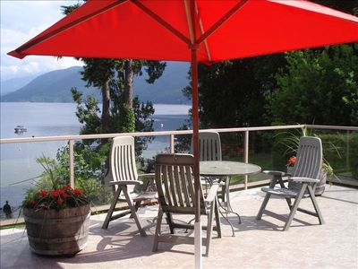 large deck with patio umbrella and chairs