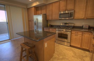 Granite counters, maple cabinets and stainless appliances in kitchen.