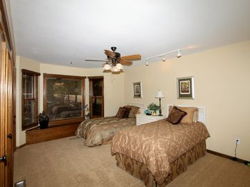 Spacious front bedroom has twin beds. Nice view out the bay window of front yard