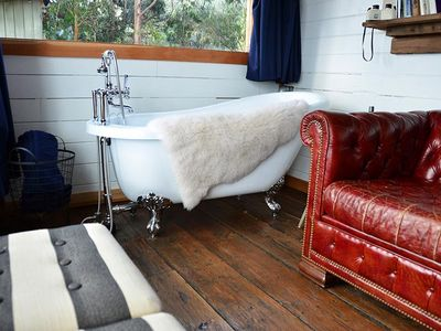Antique clawfoot tub as well as other rustic chic furnishings and finishes throughout
