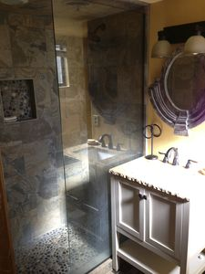 Shower is all glass/open concept with pebbled shower floors for massaging feet.