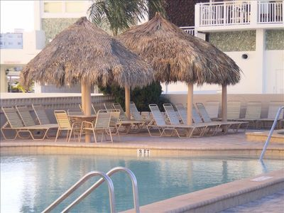 Lounge chairs line the pool along with tables and chairs for shaded coverings.