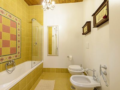Elegant bathroom of the 2 twin bedrooms w. tub/glass shower enclosure/fine tiles