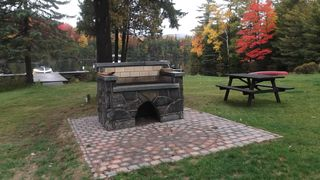 Lake Placid property rental photo - The hand hewn grill and picnic table across from boat dock.