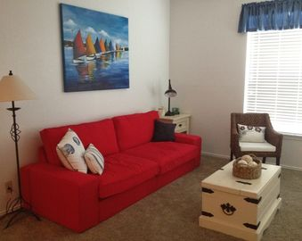 North Padre Island condo rental - Living Area. This couch rolls out to a comfortable queen size slat bed.