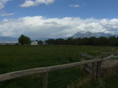 View of garage and house across pasture, with Mt. Lamborn in the distance