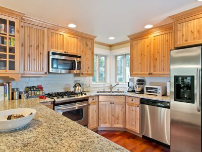 Open kitchen with granite counters, stainless appliances, and gas range