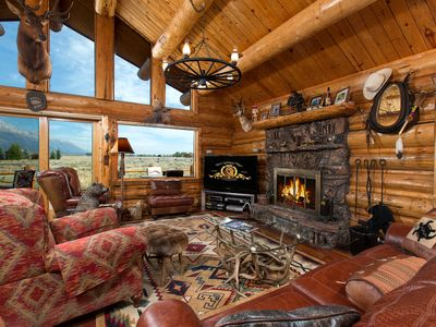 Great room with flat screen TV and river rock fireplace and wall of windows.