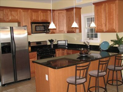 Beautiful modern kitchen with huge island and stainless steel appliances.