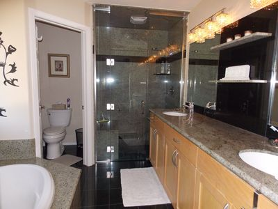 Large en suite with soaking tub, double vanity and marble step in shower.