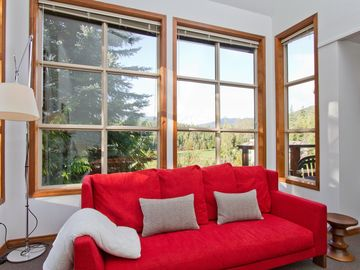 Whistler townhome rental - Living room with view of mountains and Chateau Whistler golf course