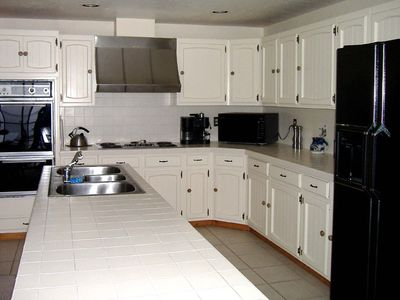 Well-stocked kitchen has double ovens, large island, and all the conveniences.
