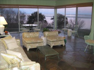 Large, wall-to-wall glass enclosed sunroom with water views.