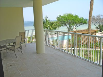 The lovely & huge porch w/ views of the bay,pool,lazy river. Table for eating.