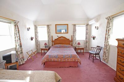 Bedroom with queen bed, and twin bed in foreground