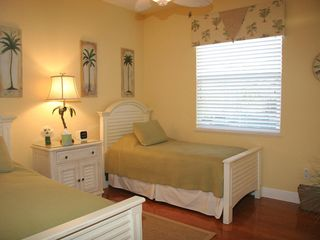 Marco Island house photo - Twin bedroom with tropical atmosphere, flat screen tv, hardwood flooring.