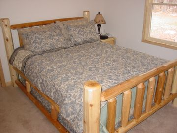 Bedroom on main level features log furniture and a queen bed.