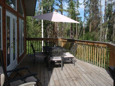 Huge deck facing the lake has umbrella with table and chairs, recliners and BBQ